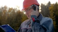 istock Builder In A Helmet Talking On The Phone Looking At The Plan Against The Sun 1089712336