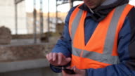 istock Builder in a white helmet with a smartphone at a construction site 1194521801