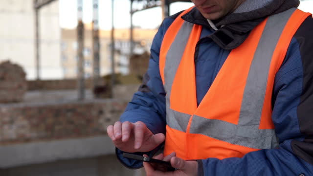 Builder in a white helmet with a smartphone at a construction site - vídeo
