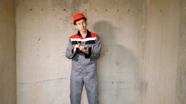 Builder in hardhat writing on clipboard Adult man in overall and orange hardhat standing in building on site taking notes on clipboard handbook stock videos & royalty-free footage