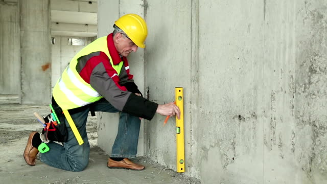 Builder in yellow hard hat with level at building site