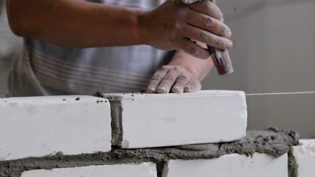 builder is doing brickwork, hitting over brick by trowel for leveling and taking off an excess cement mortar - mattone video stock e b–roll