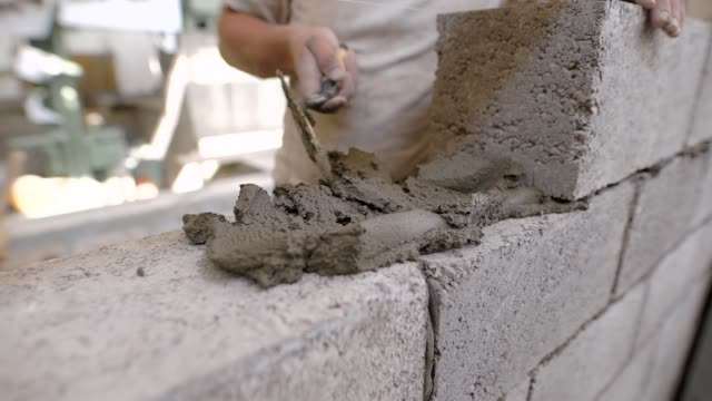builder is imposing building solution on a wall from blocks during doing brick masonry in a construction area video