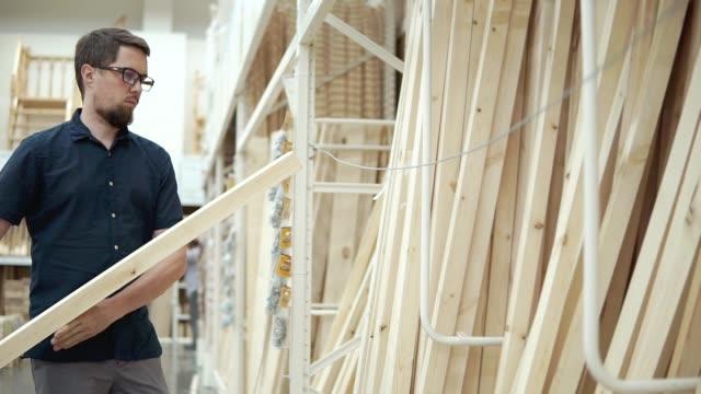 vídeos de stock e filmes b-roll de builder is selecting wooden boards in a building materials store - material de construção