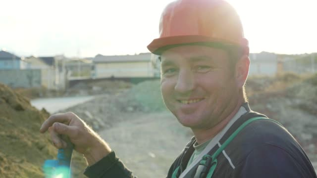 Builder looking at camera and smiling at construction site, slow motion. video