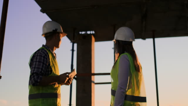Builder man with a tablet and a woman inspector in white helmets shake hands at sunset standing on the roof of the building. Symbol of agreement of successful work.