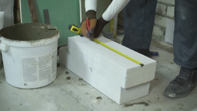 builder measures aerated concrete block with measuring tape and corner ruler