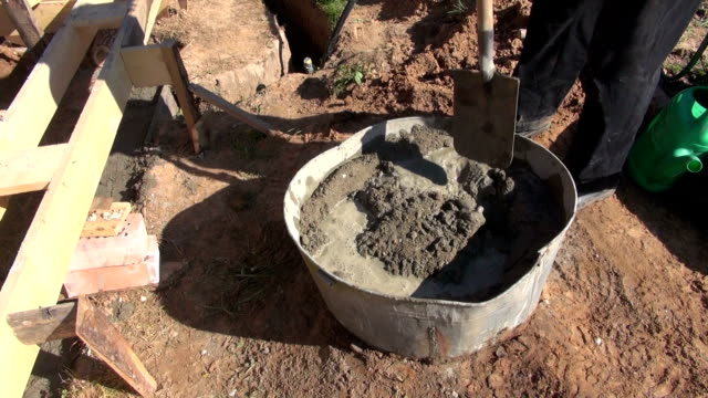Builder mixing cement with water