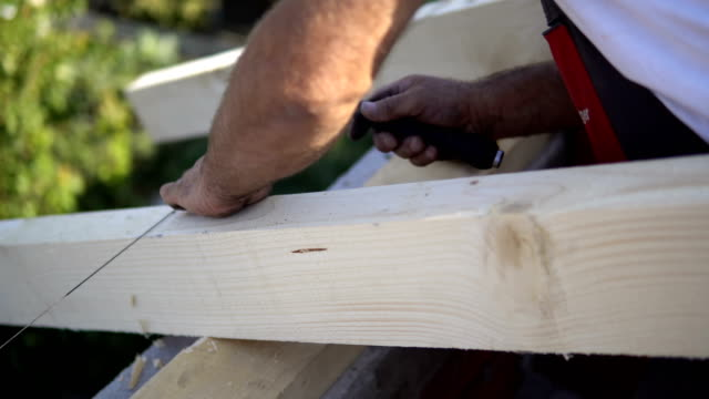 Builder nailing nails with hammer at work with wooden roof construction