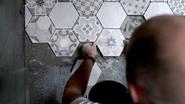 builder placing tiles on the floor - piastrella video stock e b–roll