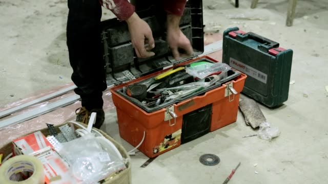 A builder puts the tools in a box.