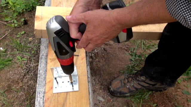 Builder screwing screws Builder screwing screws to attach metal holder with electrical drill into wooden plank on cement foundation cordless phone stock videos & royalty-free footage