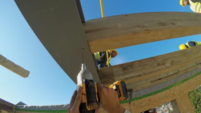 pov builder закручивает винт в поддерживающую балку - винт стоковые видео и кадры b-roll