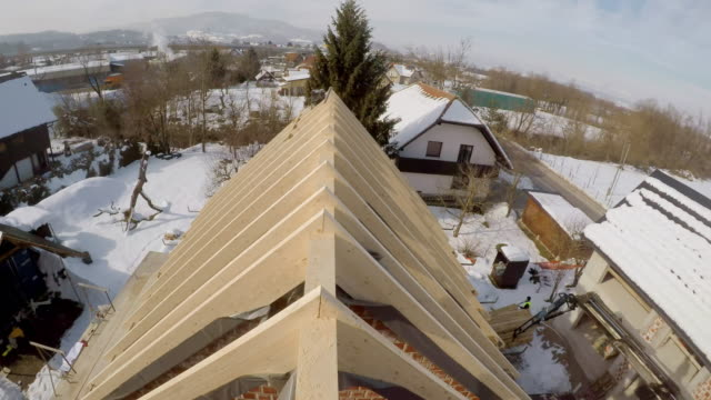 POV Builder walking across a wooden beam on the roof of the house