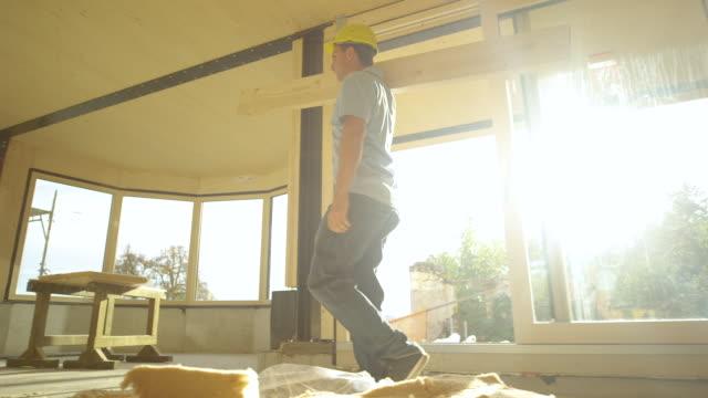 low angle builder går över ett solbelyst rum med en träpanel på axeln - solar panel bildbanksvideor och videomaterial från bakom kulisserna