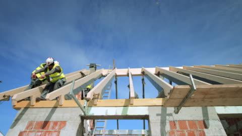 vídeos y material grabado en eventos de stock de constructores de ld colocar las vigas de madera en el techo sol - construir