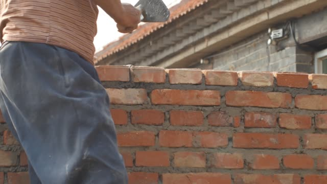 Builders build walls with red bricks