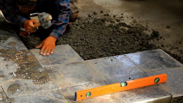 Builders doing tiled floor. video