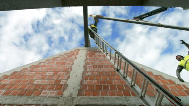 vídeos y material grabado en eventos de stock de constructores de ld, colocar una viga de madera en su lugar mientras la grúa lo sostiene en el aire - material de construcción