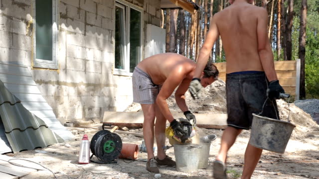 Builders prepare a construction glue in the bucket. video