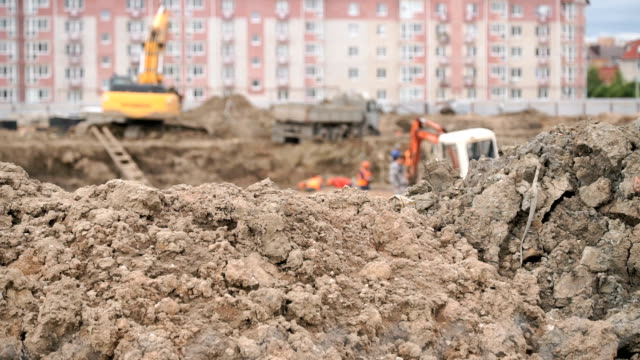 Builders work into large clay pit for construction video