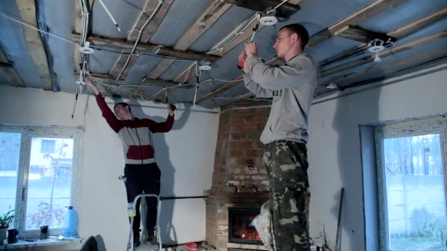Builders work with wiring on the ceiling.