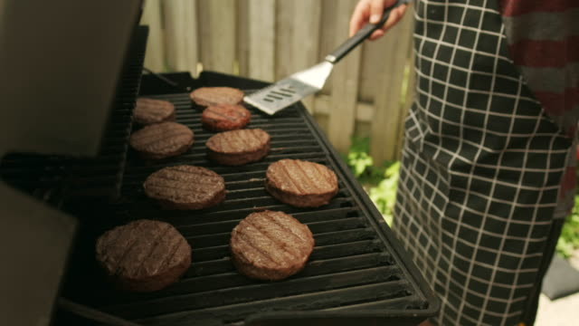 Building 4th July BBQ hamburger Hands of Chef flipping hamburgers on BBQ grill lunch outdoor at 4th July backyard celebration. fourth of july videos stock videos & royalty-free footage