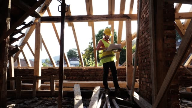 building a house roof. a confident female architect working on the roof structure on a construction site of a residential building on a bright sunny day. - ispettore della qualità video stock e b–roll