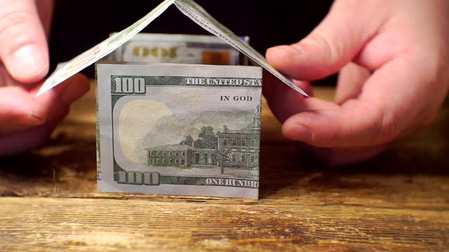 building, buying, selling or insuring real estate.business concept.hands build on the table a small house made of paper hundred dollar bills.close-up.shallow depth of field
