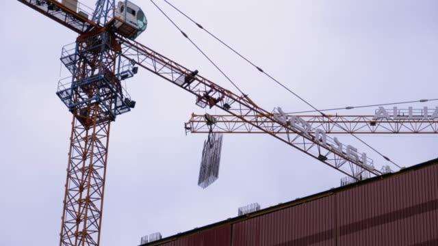 vídeos de stock, filmes e b-roll de construção de prédios. um guindaste em um canteiro de obras levanta uma carga - pesado peso