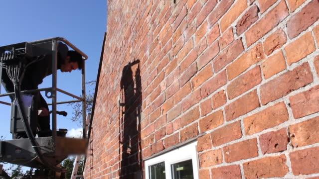 building contractor inspecting and pointing a wall - skylift bildbanksvideor och videomaterial från bakom kulisserna