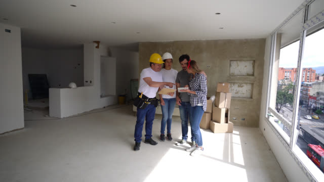 Building contractors talking to happy young couple during a home renovation looking at clipboard and tablet all smiling Building contractors talking to happy young couple during a home renovation looking at clipboard and tablet all smiling very happy renovation stock videos & royalty-free footage