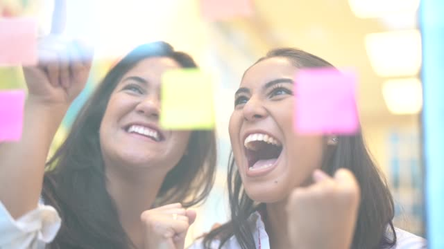 Building Creative Ideas Two business women working together on wall glass incentive stock videos & royalty-free footage