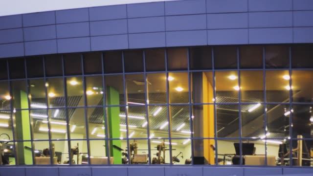 building fitness club window. night empty fitness gym - sala gimnastyczna miejsce rekreacji filmów i materiałów b-roll