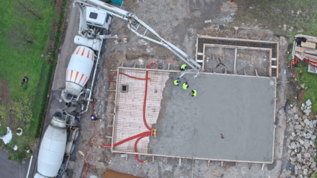 AERIAL Building foundation for the building Aerial shot of the foundation of the building being poured at the construction site. Shot in Slovenia. construction machinery stock videos & royalty-free footage