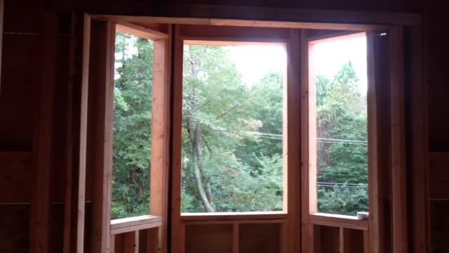 vídeos de stock e filmes b-roll de building frame structure on a new development timber frame for a progressing house. - obras em casa janelas
