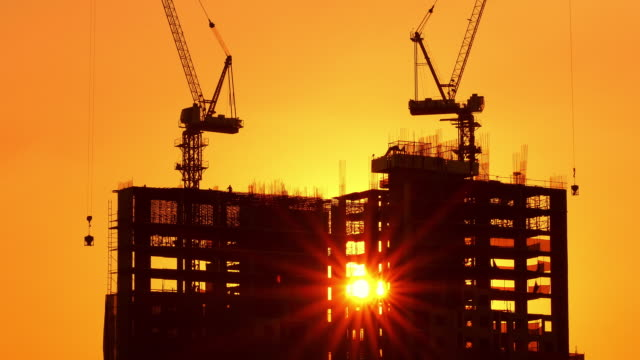 Building in the Process of Construction. In the Background Working Crane, Forest, sea and Sunset. stock video.