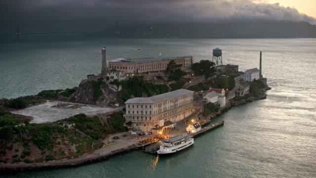 vídeos y material grabado en eventos de stock de edificio de la antena en la isla de alcatraz con sus luces encendidas al atardecer - san francisco