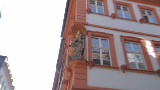 building on the corner of main street, with madonna statue - barocco video stock e b–roll