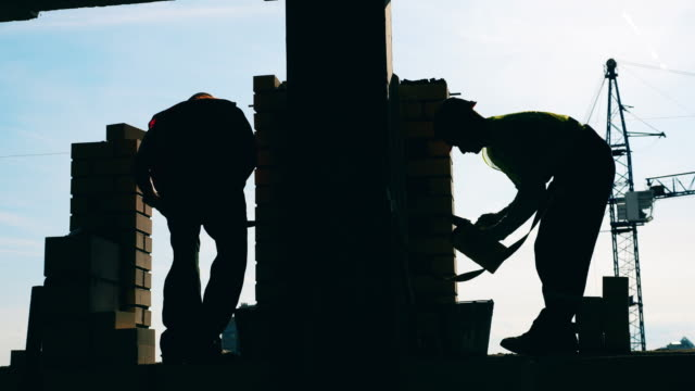Building wall is getting constructed by two backlit engineers Building wall is getting constructed by two backlit engineers. 4K foundation make up stock videos & royalty-free footage