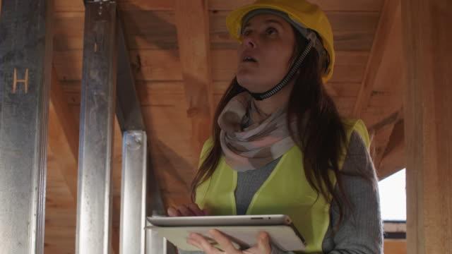 costruire la tua casa. un'architetto donna fiduciosa che lavora sulla struttura del tetto in un cantiere di un edificio residenziale in una luminosa giornata di sole. struttura del cartongesso. - ispettore della qualità video stock e b–roll
