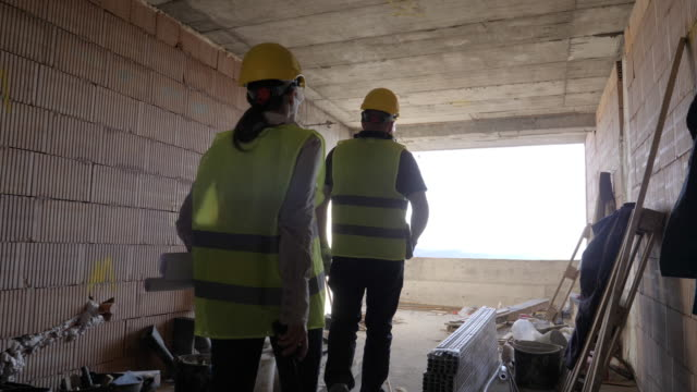 building your home. meeting of a confident female architect and a construction worker discussing and working together at construction site of a residential building on a bright sunny day. - продвижение трудовые отношения стоковые видео и кадры b-roll