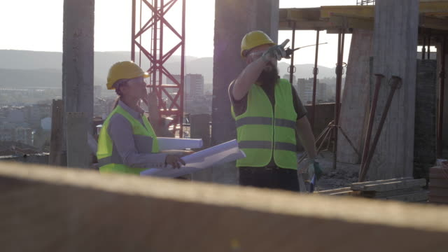 Building your home. Meeting of a Confident Female Architect and a Construction Worker Discussing and Working Together at Construction site of a Residential Building on a Bright Sunny Day. A Teamwork of an Experienced Architect - Project Manager and a Construction worker at site of a  building, checking the Progress of the Building Activity. concrete architecture stock videos & royalty-free footage