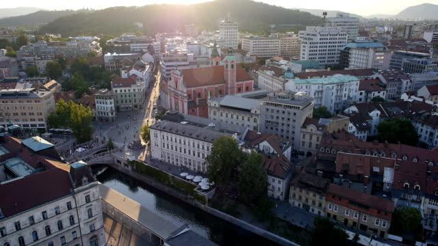 aerial: buildings, river channel and the city square at sunset - walking home sunset street bildbanksvideor och videomaterial från bakom kulisserna