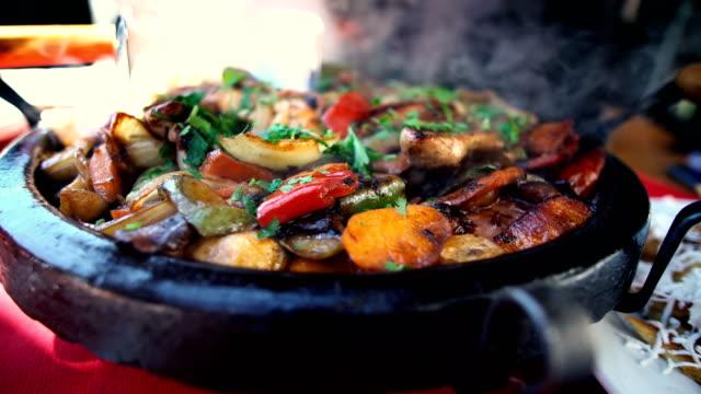 bulgariska nationalrätt-grönsaksgryta beredd och serveras i en keramisk kruka - bulgarien bildbanksvideor och videomaterial från bakom kulisserna