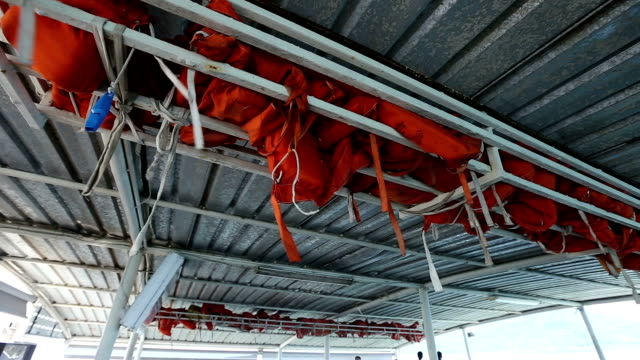 Bulk of Safety Life Vest Jacket hang keep on upper roof top of ferry boat video