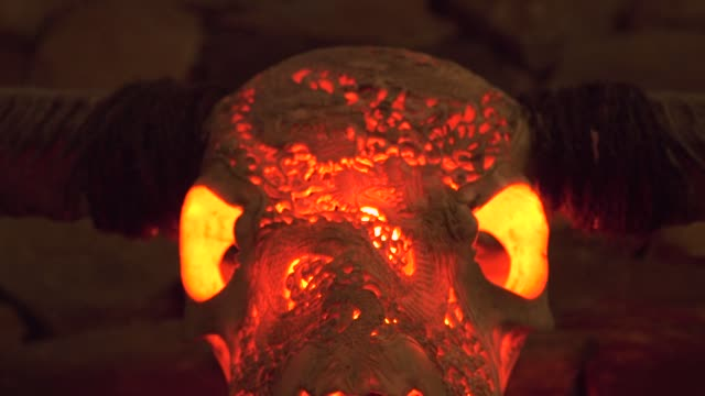 Bull skull with horns and red light from inside hanging on stone wall for interior design. Decorative hunting trophy. Buffalo skull with horn in dark room