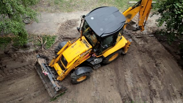 A bulldozer is leveling a piece of land. A bulldozer is leveling a piece of land after construction work. construction vehicle stock videos & royalty-free footage