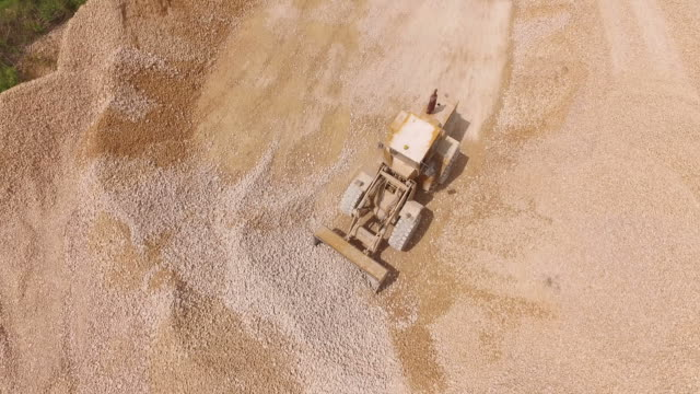 Bulldozer loading gravel and stones from the pile. Aerial video