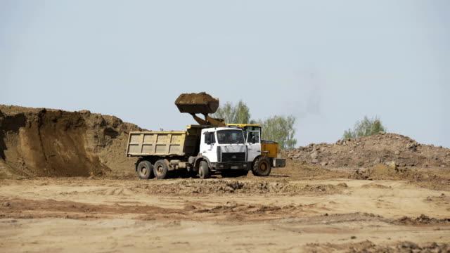 bulldozer loading sand transportation truck on construction site. construction equipment. crawler bulldozer moving sand - ghiaia video stock e b–roll
